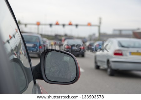 Traffic on highway captured from car window. Visible side view mirror
