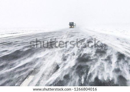 Traffic on highway in snow blizzard. Cars on snowy asphalt road drives in dangerous conditions with bad visibility and strong wind