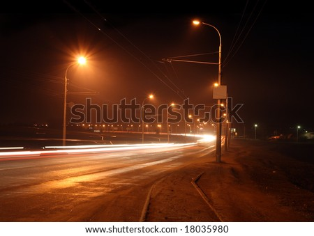 traffic on night road with street lamps in fog