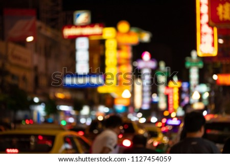 Traffic on Yaowarat Road passes below lit signs in the Chinatown district at night restaurants and street food stalls. Blur and bokeh background. #1127454059