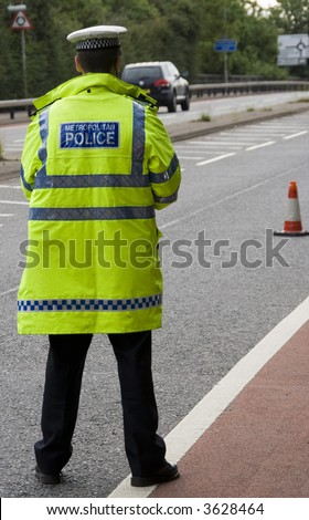 Traffic police officer waits standing in the road looking for on coming vehicles