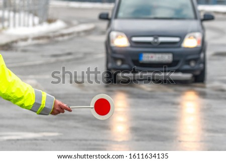 Traffic policeman stops the car. Hand of cop with stop sign.