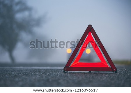 Traffic problem in thick fog. Car on the road behind warning triangle. #1216396519