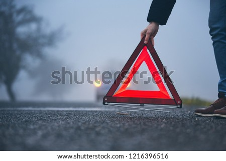 Traffic problem in thick fog. Driver putting warning triangle behind his broken car. #1216396516