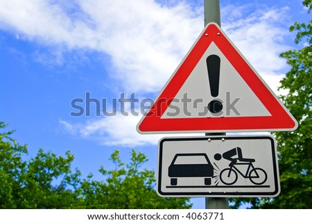 Traffic road sign with cloudy blue sky and trees