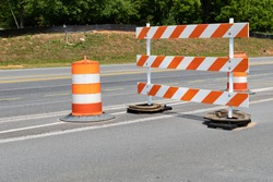Traffic safety barricade and barrels with orange and white stripes on an asphalt street, horizontal aspect