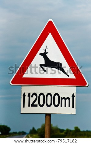Traffic sign for deer pass against blue sky