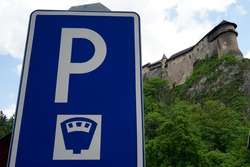 Traffic sign for paid parking in tourist area around Orava castle in Slovakia. Low angle view with the silhouette of the castle on the background.
