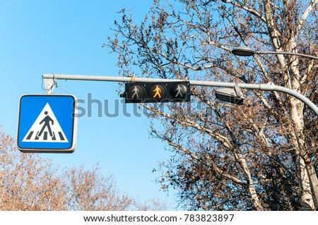 Traffic sign for pedestrians on the metal pole with electric signaling above the crosswalk and silhouette symbol of man crossing road on the board #783823897
