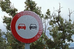 Traffic sign forbidden to overtake. Completely icy traffic sign after a small snowfall.