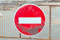 Traffic sign hangs on the fence. Roadworks. Road closed. No entry. Ban