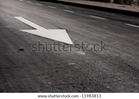 Traffic sign of obligation printed in the asphalted road. Motion blur is deliberated. The focus is in the arrow.