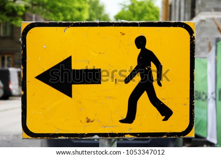 Traffic sign: on a yellow background a black silhouette of a walking man and a black arrow to the left against a city landscape background. Signs, symbols. #1053347012