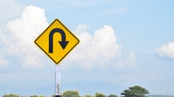 Traffic sign: Right U-turn sign on cement pole beside the rural road with white cloudy bluesky background, copy space.