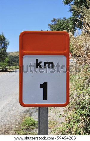 Traffic sign that indicates one kilometer distance from here