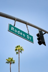 Traffic sign with overhead traffic light at Rodeo Drive, the street known for its luxury goods stores in Beverly Hills, Los Angeles.