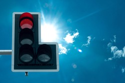 Traffic signal boards that appear red lights to stop. under background of blue sky with sunlight.