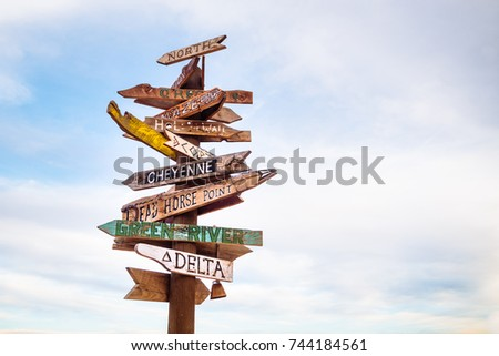Traffic signs and directional signpost pointing to famous tourist destinations in Utah with cloudy sky and free copy space for text #744184561