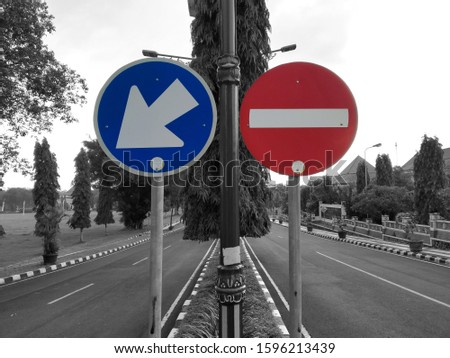 Traffic signs with road directions must enter the left lane and entry restrictions on the right lane, with black and white background of sky and perspectives from roads, trees, pole and buildings.