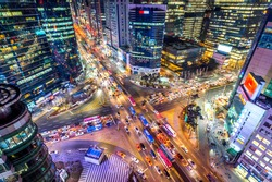 Traffic speeds through an intersection at night in Gangnam, Seoul in South Korea.
