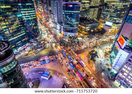 Traffic speeds through an intersection at night in Gangnam, Seoul in South Korea. #715753720