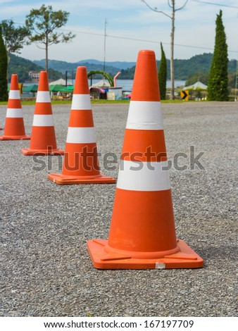 traffic warning cone in row to separate route in parking area