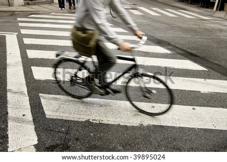 Traffic with speedy cyclist passing crosswalk.