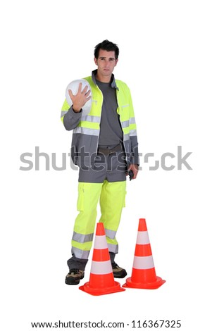Traffic worker stood by cone