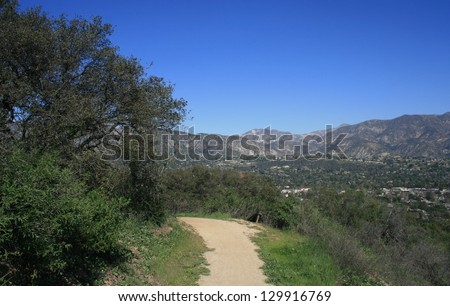 Trail along a hill side with mountains in the distance, California