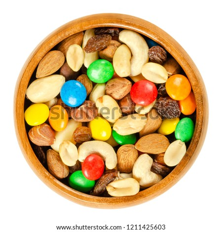 Trail mix in wooden bowl. Snack mix. Almonds, cashews, peanuts, hazelnuts, raisins and colorful chocolate candies. Food to be taken along hikes. Macro food photo closeup from above on white background