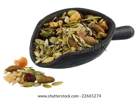 trail mix with pumpkin, sunflowers seeds, almonds, dried papaya,  cranberries, raisins and apples on a rustic wooden scoop isolated on white