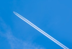 Trail of white smoke from the airplane on the blue sky