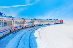 Trail of white smoke from the airplane -Red diesel train (East express) in motion at the snow covered railway platform - The train connecting Ankara to Kars - Turkey