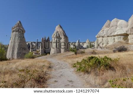 trail passing giant sandstone hoodoos in Love Valley (Baglidere Vadisi) Goreme, Nevsehir province, Turkey
