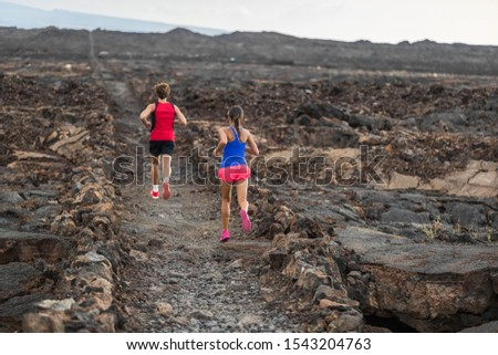 Trail run runners couple fit athletes training together running in volcanic field for marathon race. Male and female people endurance workout.