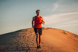 Trail runner athlete running man in desert sand dun in heat of summer sunset day.