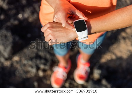Trail runner athlete using her smart watch app to monitor fitness progress or heart rate during run cardio workout. Woman training outdoors on mountain rocks. Closeup of tech gear.