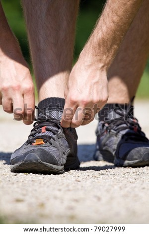 Trail runner in summer nature tying sport shoes, running concept
