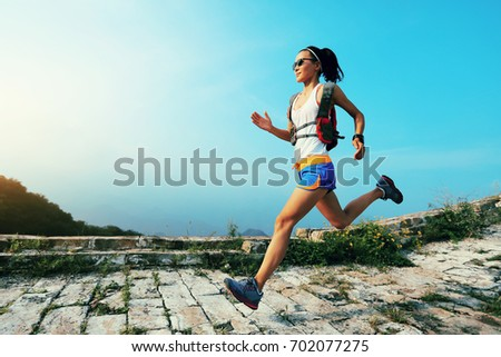 trail runner woman running at great wall on the top of mountain #702077275