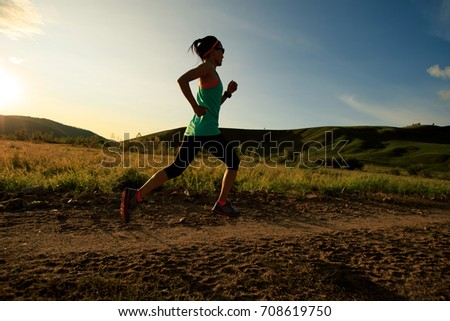 trail runner woman running on forest trail #708619750