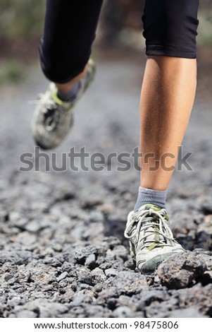 Trail runner woman running on mountain path with rocks. Running shoes and legs closeup of female fitness sport model during outdoor workout.