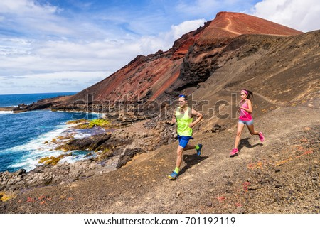 Trail running couple runners racing on mountain path in volcanic rocks nature landscape in summer outdoor. Ultra running race run.