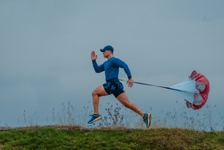 Trail running man with resistance parachute on path exercising