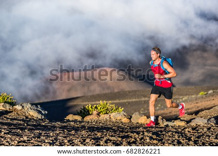 Trail running runner man on endurance run with backpack on volcano mountain. Ultra marathon race athlete on volcanic rocks path in mountains landscape. #682826221