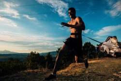 Trail running silhouette man with resistance parachute on mountain path exercising. Strong man running using resistance parachute outdoors. Young Caucasian man in black sports clothing running.