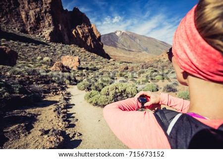 Trail running woman on mountain trail looking at sportwatch, checking performance, heart pulse or GPS position nd track. Cross country running in beautiful nature, Canary Islands.