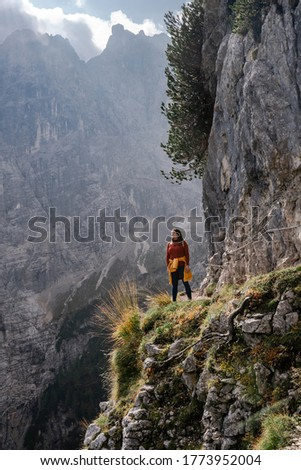 Trail to Sorapis. Dolomite Alps. Italy. Travel girl stays on alpine path over a cliff surrounded by rocks and greenery on background of high rock mountain wall & sunny clouds on the blue sky