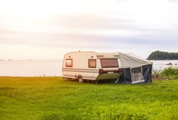 Trailer motor home and a tent on the grassy part of the beach at sunset. Leisure mobile camping home for tourists overlooking the blue sea and cape. Adventure relaxing travel on caravan van