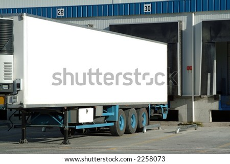 Trailer of truck sitting at a loading dock.