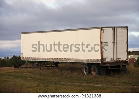 Trailer resting on the grass - seen during afternoon - stock photo